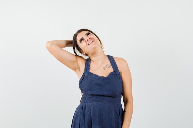 Jovem, mantendo a mão levantada atrás da cabeça em um vestido e parecendo atraente