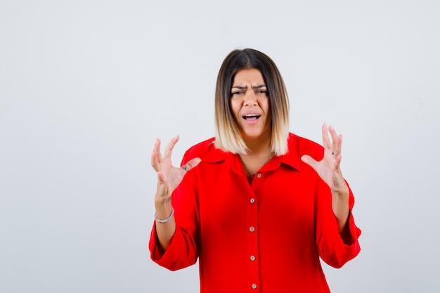 Jovem, mantendo as mãos de maneira agressiva em uma camisa vermelha grande demais e parecendo irritada. vista frontal.