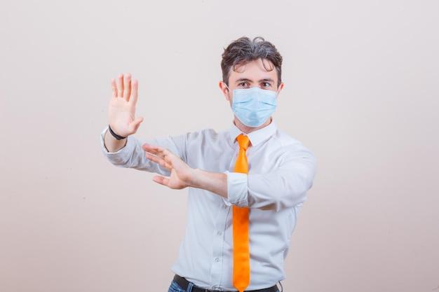 Jovem mantendo as mãos para se defender com camisa, gravata, máscara e parecendo preocupado