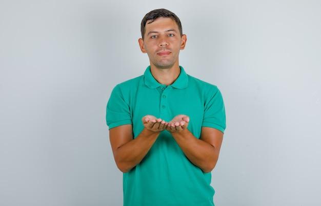 Jovem, mantendo as palmas das mãos em concha vazias juntas em t-shirt verde. vista frontal.