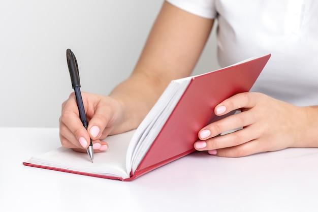 Jovem mão feminina escreve notas no caderno, planejando sua agenda na mesa branca