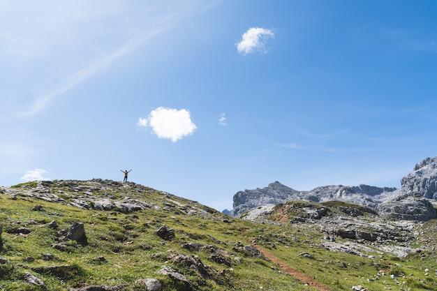 Jovem mãos ao alto no topo de uma montanha