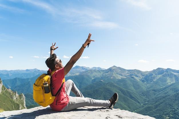 Jovem mãos levantadas sentado no topo de uma montanha