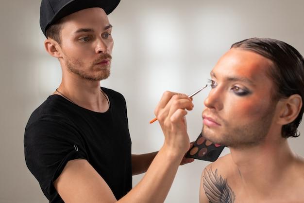 Jovem maquiador com pincel ou aplicador aplicando sombra cinza nas pálpebras de modelo masculino com tatuagem no ombro