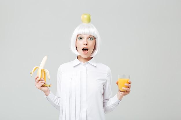 Jovem maravilhada com uma maçã na cabeça, segurando uma banana e um copo de suco