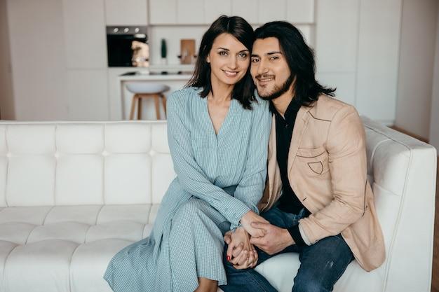 Jovem marido abraça gentilmente sua esposa na sala de estar