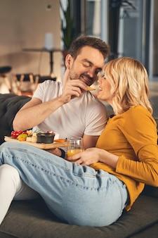 Jovem marido adorável alimentando sua esposa faminta com uma fatia de queijo parmesão no café da manhã
