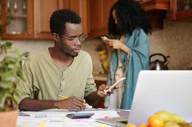 Jovem marido de pele escura sentado à mesa da cozinha com papéis, calculadora e laptop, cuidando da papelada e calculando as despesas da família usando o celular