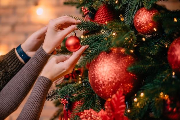 Jovem marido e mulher decorando uma árvore de natal juntos