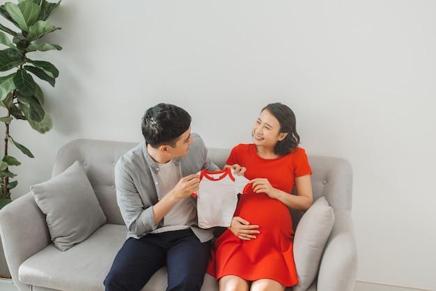Jovem marido e uma esposa grávida mostram sua camiseta de bebê quando estão sentados no sofá.