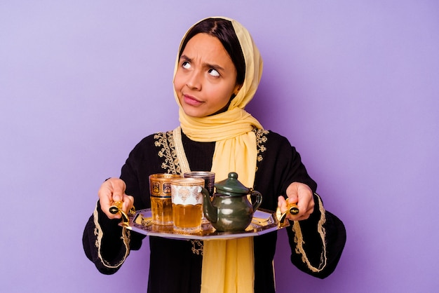 Jovem marroquina segurando um copo de chá isolado em um fundo roxo
