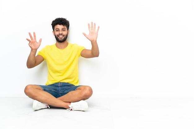 Jovem marroquino bonito sentado no chão sobre um fundo isolado, contando nove com os dedos