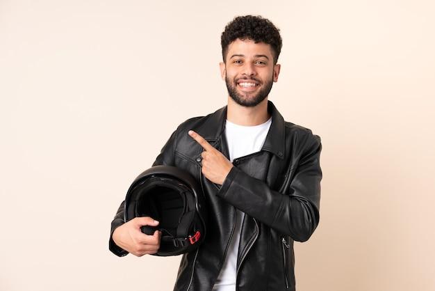 Jovem marroquino com capacete de motociclista isolado em parede bege apontando para o lado para apresentar um produto