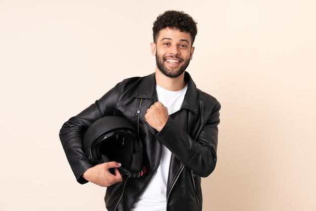 Jovem marroquino com capacete de motociclista isolado na parede bege comemorando vitória