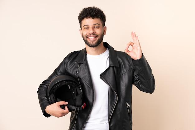 Jovem marroquino com capacete de motociclista isolado na parede bege, mostrando sinal de ok com os dedos