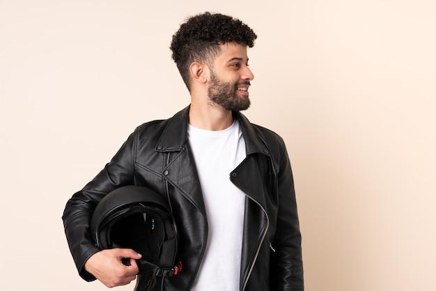 Jovem marroquino com capacete de motociclista isolado na parede bege olhando para o lado
