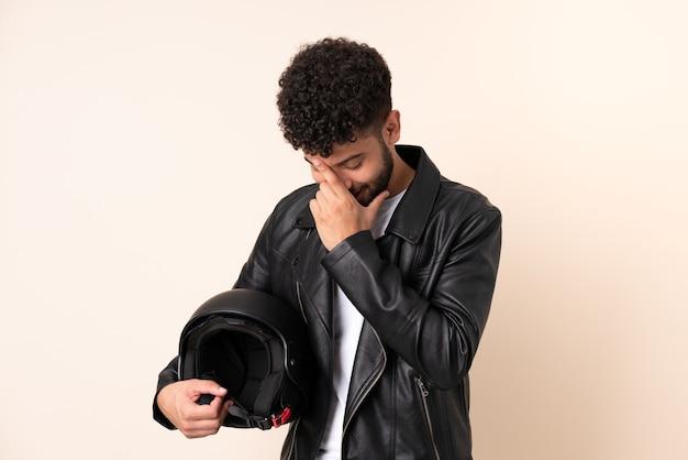 Jovem marroquino com capacete de motociclista isolado numa parede bege a rir