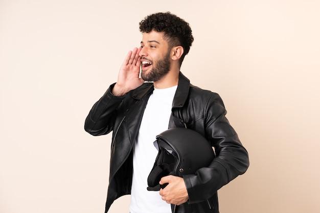Jovem marroquino com um capacete de motociclista isolado em uma parede bege, gritando com a boca aberta para o lado