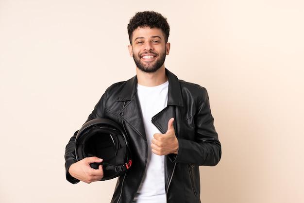 Jovem marroquino com um capacete de motociclista isolado na parede bege fazendo um gesto de polegar para cima