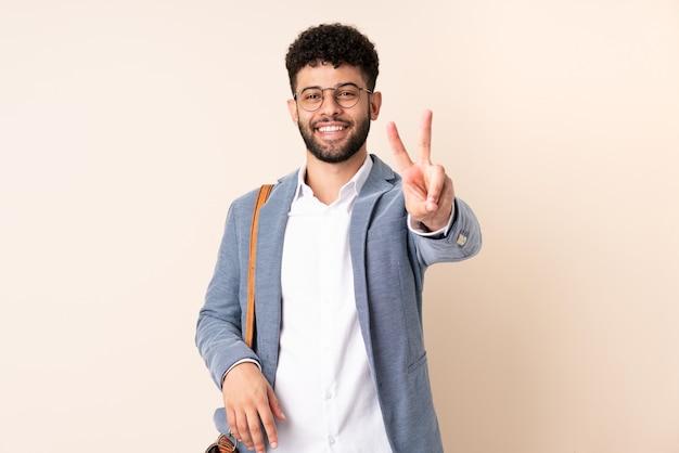 Jovem marroquino, empresário, isolado em um bege, sorrindo e mostrando sinal de vitória