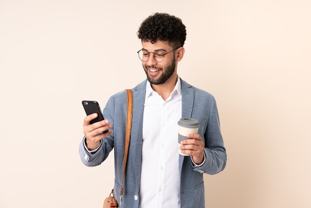 Jovem marroquino, empresário, isolado em um fundo bege, segurando um café para levar e um celular
