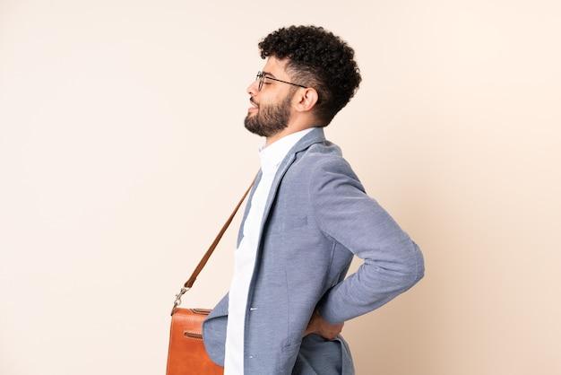 Jovem marroquino, empresário, isolado em um fundo bege, sofrendo de dor nas costas por ter feito um esforço