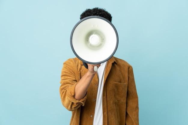 Jovem marroquino isolado em uma parede azul gritando em um megafone para anunciar algo