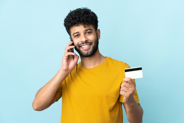 Jovem marroquino isolado na parede azul, conversando com o celular e segurando um cartão de crédito