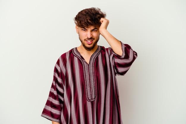 Jovem marroquino isolado na parede branca, esquecendo algo, batendo na testa com a palma da mão e fechando os olhos.