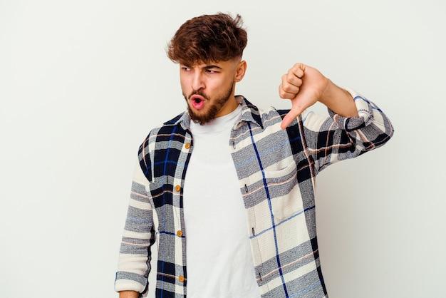 Jovem marroquino isolado no branco, mostrando o polegar para baixo e expressando antipatia.
