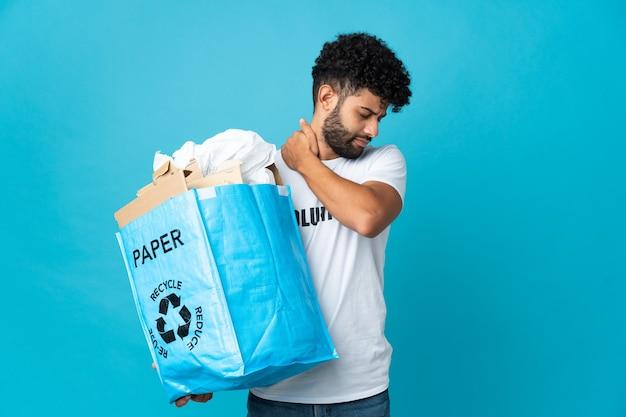Jovem marroquino segurando uma sacola de reciclagem cheia de papel para reciclar sobre um fundo isolado sofrendo de dor no ombro por ter feito um esforço