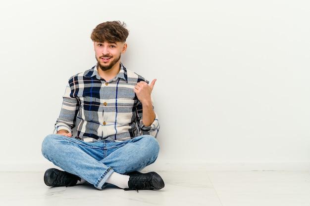 Jovem marroquino sentado no chão chocado a apontar com o dedo indicador
