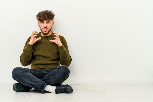 Jovem marroquino sentado no chão, isolado no branco chateado, gritando com as mãos tensas.