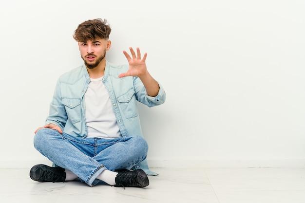 Jovem marroquino sentado no chão isolado no branco, mostrando garras imitando um gato, gesto agressivo.