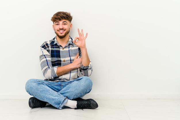 Jovem marroquino sentado no chão isolado no branco pisca os olhos e segura um gesto de ok com a mão.