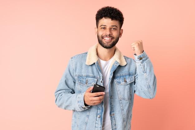 Jovem marroquino usando celular isolado na parede rosa comemorando vitória