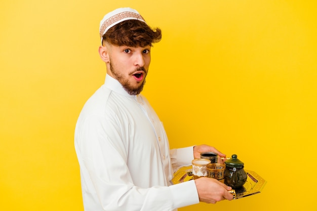 Jovem marroquino vestindo o típico traje árabe bebendo chá isolado em amarelo