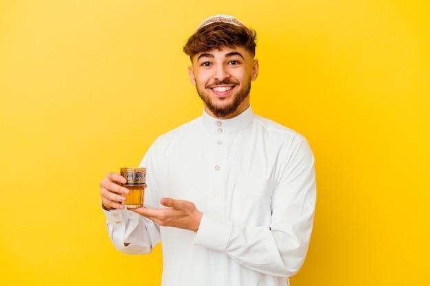 Jovem marroquino vestindo o típico traje árabe bebendo chá isolado na parede amarela