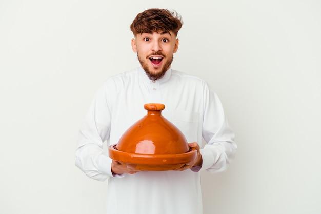 Jovem marroquino vestindo o típico traje árabe, segurando um tajine, recebendo uma agradável surpresa, animado e levantando as mãos.
