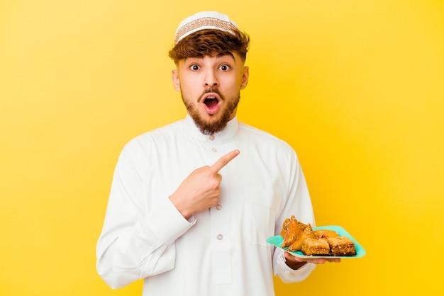 Jovem marroquino vestindo o traje árabe típico comendo doces árabes isolados em amarelo apontando para o lado