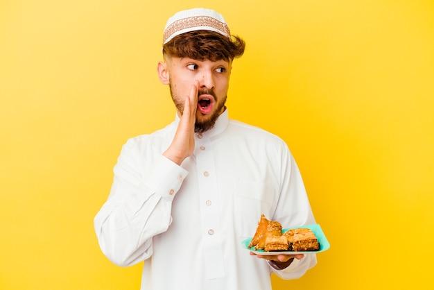 Jovem marroquino vestindo o traje árabe típico comendo doces árabes isolados no amarelo está contando uma notícia secreta da travessia e olhando para o lado