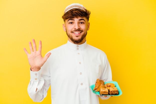Jovem marroquino vestindo o traje árabe típico, comendo doces árabes isolados no amarelo, sorrindo alegre mostrando o número cinco com os dedos.