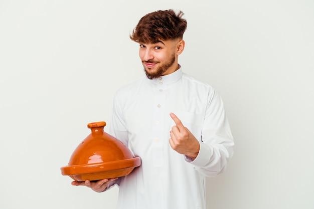 Jovem marroquino vestindo o traje árabe típico, segurando um tajine isolado no branco, apontando com o dedo para você como se fosse um convite para se aproximar.