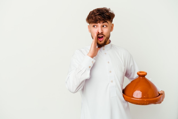 Jovem marroquino, vestindo o traje árabe típico, segurando um tajine isolado no branco, contando uma notícia secreta da travessia e olhando para o lado