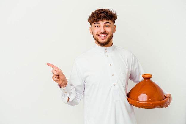 Jovem marroquino vestindo o traje árabe típico, segurando um tajine isolado no branco, sorrindo e apontando para o lado, mostrando algo no espaço em branco.