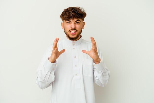 Jovem marroquino vestindo uma roupa típica árabe, isolado no fundo branco chateado gritando com as mãos tensas.