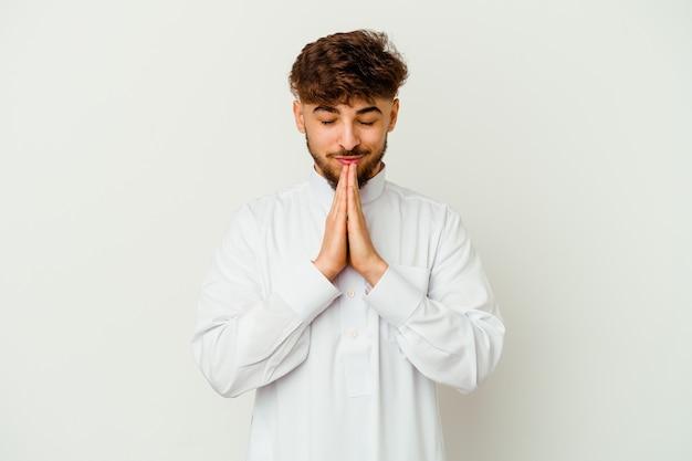 Jovem marroquino vestindo uma roupa típica árabe, isolado no fundo branco, orando de mãos dadas perto da boca, sente-se confiante.