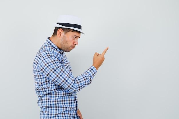Jovem masculino avisando com o dedo em uma camisa xadrez