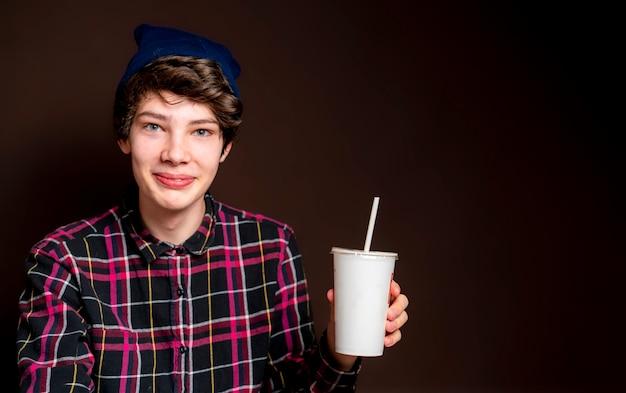 Jovem masculino beber limonada em fundo escuro isolado f