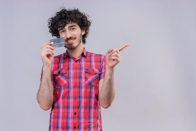 Jovem masculino cabelo cacheado isolado camisa colorida cartão do banco sorrindo e apontando